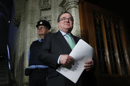 Canada's Finance Minister Jim Flaherty speaks to journalists while walking to the House of Commons on Parliament Hill in Ottawa December 9, 2013. REUTERS/Chris Wattie