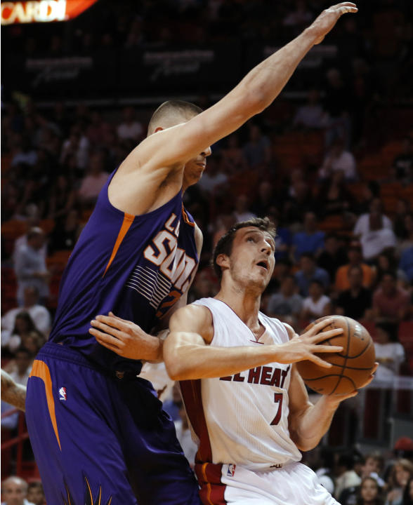 Miami Heat guard Goran Dragic (7) is fouled by Phoenix Suns center Alex Len during the first quarter of an NBA basketball game, Monday, March 2, 2015. in Miami. (AP Photo/Joe Skipper)
