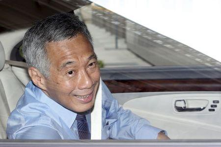 Singapore's PM Lee winds down window to wave to photographers as he arrives for damages hearing against blogger Roy Ngerng at the Supreme Court in Singapore