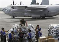 Philippine and U.S. military personnel prepare to load relief goods on a U.S. C-130 plane for victims of Typhoon Haiyan that hit the central Philippines, at Villamor Air Base in Manila November 11, 2013. REUTERS/Cheryl Ravelo