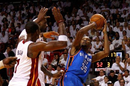 Oklahoma City Thunder's Kevin Durant attempts a shot as Miami Heat's Chris Bosh (L) defends during game four