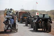 (LtoR) A local truck passes a convoy of French army vehicles heading towards Gao on February 7, 2013. French-led forces continue to come under attack in reclaimed territory, including rocket fire directed at them Tuesday in Gao, the largest city in the north