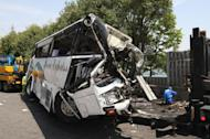 Policemen inspect a sightseeing bus after it crashed into a wall on the Kanetsu Express Way in Fujioka, some 100 km northwest of Tokyo, on April 29. Seven people were killed and 39 injured in the accident