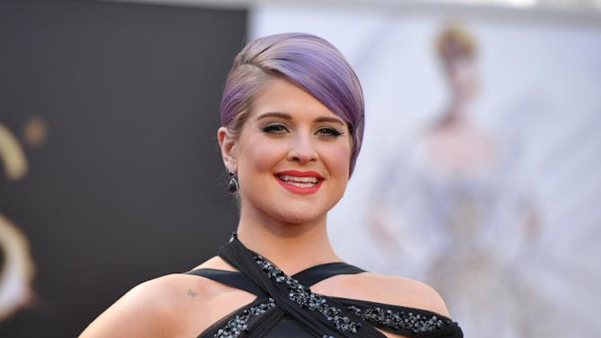 "FILE - In this Sunday, Feb. 24, 2013 file photo, TV personality Kelly Osbourne arrives at the 85th Academy Awards at the Dolby Theatre in Los Angeles.  Osbourne has been hospitalized after fainting on the set of E!'s ""Fashion Police."" A spokeswoman for Osbourne told the cable network Thursday, March 7, 2013, that the 28-year-old TV personality is awake, alert and in stable condition, and she will be staying overnight for observation as a precautionary measure.  (Photo by John Shearer/Invision/AP, File)"