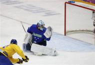 Sweden's Loui Eriksson (L) scores on Slovenia's goalie Robert Kristan during the third period of their men's quarter-finals ice hockey game at the 2014 Sochi Winter Olympic Games, February 19, 2014. REUTERS/Grigory Dukor