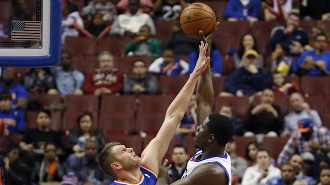 Philadelphia 76ers' Henry Sims, right, goes up for a shot against New York Knicks' Cole Aldrich during the first half of an NBA basketball game, Friday, March 21, 2014, in Philadelphia