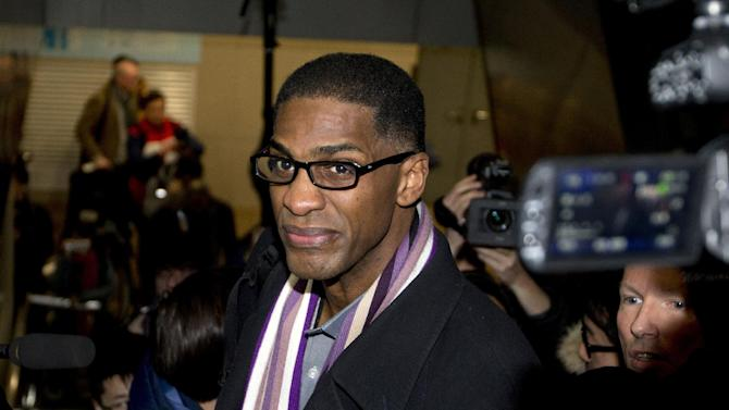 Former NBA basketball star Charles D. Smith is mobbed by journalists on an escalator upon arrival at the Beijing Capital International Airport in Beijing from Pyongyang, North Korea, Friday, Jan. 10, 2014. A squad of former basketball stars led by Dennis Rodman had a friendly game with North Korean basketball players in Pyongyang
