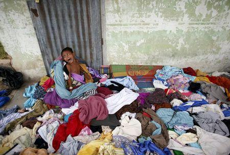 A young Rohingya migrant who arrived in Indonesia last week by boat cries while playing in a pile of clothes at a temporary shelter in Aceh Timur regency near Langsa in Indonesia's Aceh Province