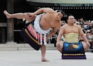 Accompanied by sumo wrestler Takarafuji (right), new yokozuna, or grand champion, Harumafuji performs the ceremonial entrance into the ring at Meiji Shrine in Tokyo in September