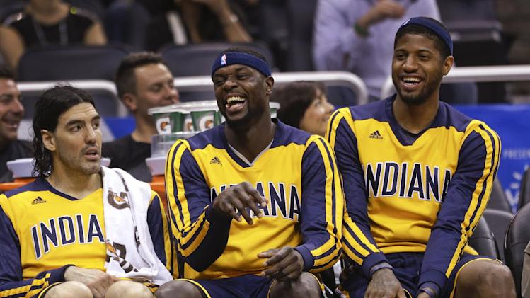 Indiana Pacers players, from left, Luis Scola, Lance Stephenson and Paul George share a laugh on the bench during the fourth quarter of an NBA basketball game in Orlando, Fla., Wednesday, April 16, 2014. Indiana won 101-86
