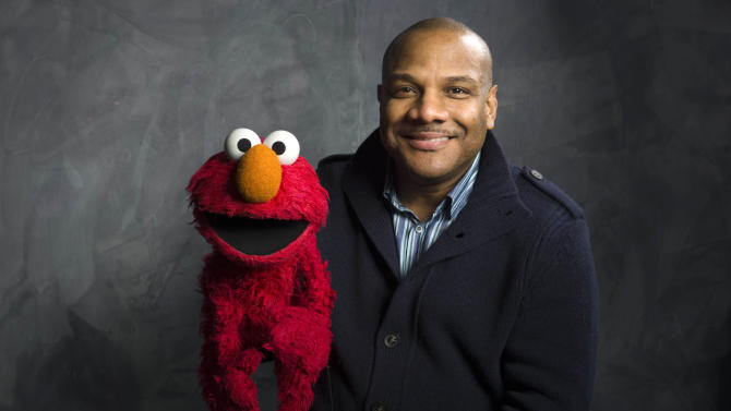 """FILE - In this Jan. 24, 2011 file photo, Elmo puppeteer Kevin Clash poses with the """"Sesame Street"""" muppet in the Fender Music Lodge during the 2011 Sundance Film Festival in Park City, Utah. Sesame Workshop says Elmo puppeteer Kevin Clash has resigned from """"Sesame Street"""" in the wake of allegations that he had sex with an under-aged youth. Last week a man accused Clash of having sex with him when he was a teenage boy, a charge Clash denied. A day later, the man recanted his charge. A lawsuit by a second accuser was filed Tuesday, Nov. 20, according to attorney Cecil Singleton. (AP Photo/Victoria Will, File)"""