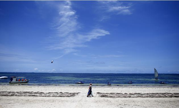 File photo of a woman walking by the beach of Kenya's coastal city of Mombasa