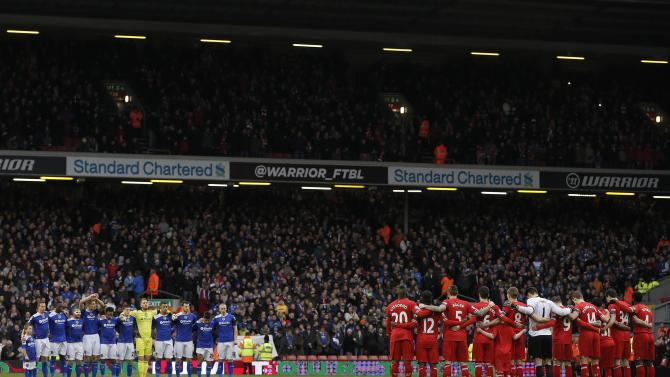 Oldham Athletic players and Liverpool players stand during a minute's silence in honour of former Oldham Athletic and Liverpool player Wayne Harrison and Portuguese great Eusebio during their FA Cup third round soccer match at Anfield in Liverpool