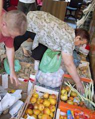 """People fill up bags with fruits and vegetables for distribution to needy people in a working class neighbourhood of Madrid, on June 1. The """"indignants"""" are currently building an extraordinary street-level network to help those hardest hit by economic hardship"""