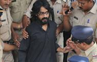 Cartoonist Aseem Trivedi, who has been arrested on sedition charges, is escorted out of the Bandra Metropolitan Magistrate court in Mumbai on September 10, 2012. India's government is facing a mounting domestic and international backlash over the arrest as critics accused it of using colonial era laws to crush dissent