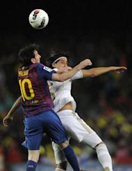 "Barcelona's forward Lionel Messi (L) jumps for the ball with Real Madrid's midfielder Sami Khedira during the Spanish League ""El Clasico"" football match at the Camp Nou stadium in Barcelona. Real Madrid won 2-1"