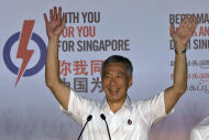 FILE - In this Sept. 12, 2015 file photo, Singapore's Prime Minister Lee Hsien Loong of the ruling People's Action Party celebrates a win in his constituency in Singapore. Less than three weeks after a landslide general election win by the ruling party, Singapore announced a new Cabinet structure Monday, Sept. 28, 2015 in a pitch for leadership renewal, with some senior officeholders taking on wider coordinating roles overseeing younger ministers. (AP Photo/Ng Han Guan, File)