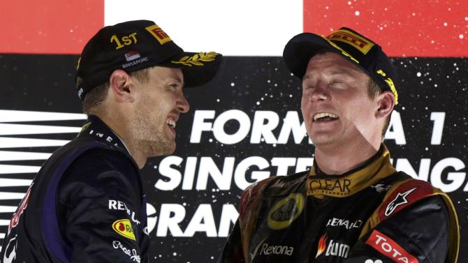 Red Bull Formula One driver Vettel celebrates on the podium with Lotus F1 Formula One driver Raikkonen after the Singapore F1 Grand Prix in Singapore