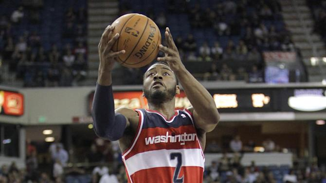 Sacramento Kings guard Isaiah Thomas, right, draws a charging foul against Washington Wizards guard John Wall during the overtime of an NBA basketball game in Sacramento, Calif., Tuesday, March 18, 2014.  The Kings won in overtime 117-111