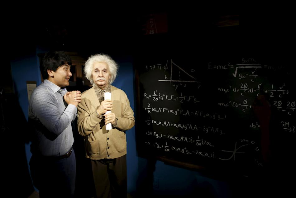 A man jokes next to the wax figure of Albert Einstein at Grevin Wax Museum in central Seoul