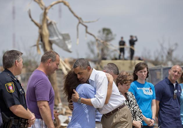 President Barack Obama embraces a school official as he views the devastation of the Plaza Towers Elementary School, Sunday, May 26, 2013, in Moore, Okla., caused by a tornado and severe weather last