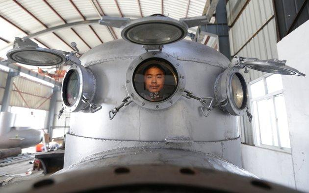 Zhang Wuyi sits in his newly made multi-seater submarine at his new workshop near an artificial pool in Wuhan, Hubei province, November 14, 2012. Zhang, a 37-year-old local farmer, who is interested i