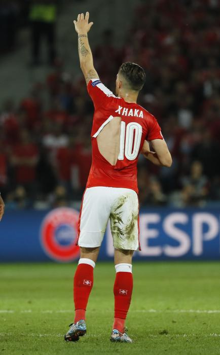 Switzerland's Granit Xhaka rips his shirt