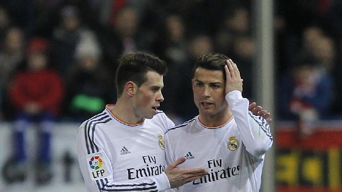 Real's Cristiano Ronaldo talks to Gareth Bale, after Ronaldo fouls Atletico's Javi Manquillo during a semi final, 2nd leg, Copa del Rey soccer match between Atletico de Madrid and Real Madrid at the Vicente Calderon stadium in Madrid, Spain, Tuesday, Feb. 11, 2014
