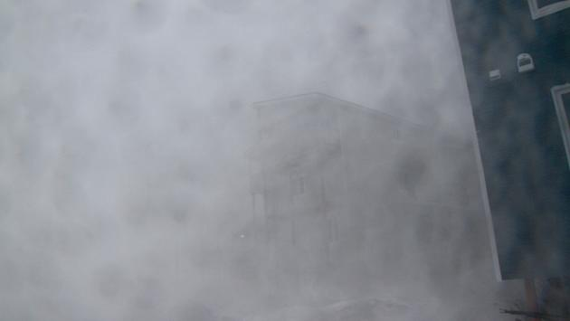 Apartment buildings are barely visible in a windstorm that's battering Iqaluit, Nunavut. Environment Canada says winds are gusting as high as 130 km/h.