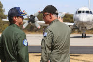 Commander Hidetsugu Iwamasa, left, of the Japan Maritime Self-Defense Force talks with Royal Australian Air Force Group Commander Craig Heath before a Japanese P-3C Orion's departure from the RAAF Pearce Base to commence a search for possible debris from the missing Malaysia Airlines flight MH370, in Perth, Australia, Monday, March 24, 2014. Satellite images released by Australia and China had earlier identified possible debris in an area that may be linked to the disappearance of the flight on March 8 with 239 people aboard. (AP Photo/Paul Kane, Pool)