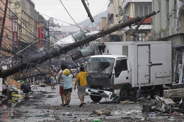Survivors walk under a fallen electric post after super Typhoon Haiyan battered Tacloban city, central Philippines November 10, 2013. One of the most powerful storms ever recorded killed at least 10,000 people in the central Philippines, a senior police official said on Sunday, with huge waves sweeping away entire coastal villages and devastating the region's main city. Super typhoon Haiyan destroyed about 70 to 80 percent of the area in its path as it tore through Leyte province on Friday, said police chief superintendent Elmer Soria. As rescue workers struggled to reach ravaged villages along the coast, where the death toll is as yet unknown, survivors foraged for food as supplies dwindled or searched for lost loved ones. REUTERS/Romeo Ranoco (PHILIPPINES - Tags: DISASTER TPX IMAGES OF THE DAY ENVIRONMENT)
