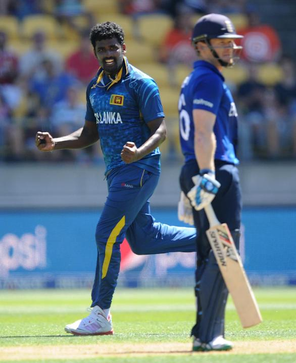 Sri Lankan bowler Thisara Perera, left, celebrates after taking the wicket of England's captain Eoin Morgan, left, during their Cricket World Cup match in Wellington, New Zealand, Sunday, March 1, 201
