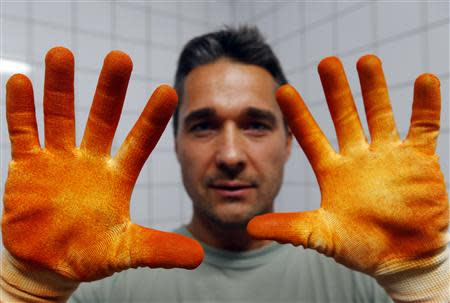Paprika maker Szabo shows his pepper-stained gloves in Batya