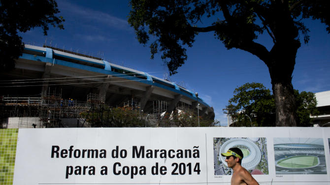 "ADVANCE FOR USE WEEKEND OF DEC. 31-JAN 1 AND THEREAFTER- FILE - In this Dec. 21, 2011, file photo, a man runs by a sign that reads in Portuguese ""Reform of Maracana for the 2014 World Cup"" outside Maracana stadium in Rio de Janeiro. The Maracana, the second-most visited tourist destination in Rio, is to soccer what Yankee Stadium is to baseball, what Lambeau Field is to NFL football or what Madison Square Garden is to basketball. (AP Photo/Victor R. Caivano)"