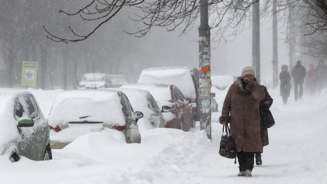 People walk through snowy streets in Kiev, Ukraine, Saturday, March. 23, 2013. Heavy snow storms from the Balkan region have hit Ukraine since last afternoon, in a last attack by winter at the end of the first spring month. The temperature in the Ukrainian capital is about -8 Celsius (18 F) on Saturday.(AP Photo/Sergei Chuzavkov)