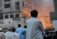Anxious relatives and local residents watch the rescue operation at a garment factory in Karachi on Wednesday. A huge fire at a garment factory in Pakistan's largest city of Karachi has killed at least 240 people, Karachi city's police chief Iqbal Mehmood, told AFP