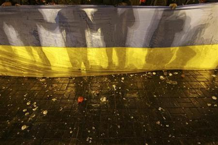 Participants of an anti-war rally hold a national flag as eggs thrown by pro-Russia protesters cover the floor during their clashes in Donetsk March 13, 2014. REUTERS/Stringer