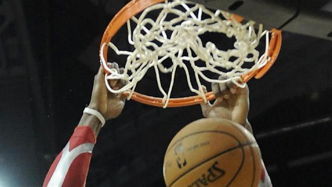 Houston Rockets' Dwight Howard hangs on the rim after dunking the ball against the Cleveland Cavaliers in the second half of an NBA basketball game Saturday, Feb. 1, 2014, in Houston. The Rockets won 106-92