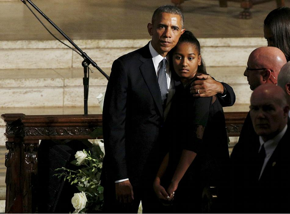 U.S. President Obama hugs daughter Sasha as the casket of former Delaware Attorney General Beau Biden, son of Vice President Biden, leaves his funeral in Wilimington, Delaware