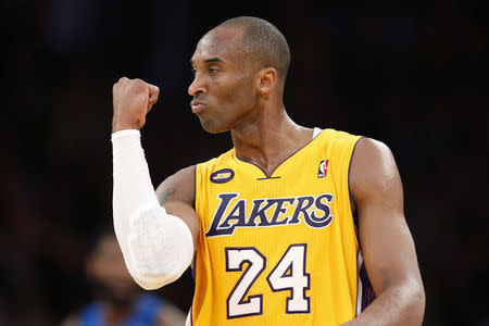 Los Angeles Lakers' Bryant celebrates after his teammate Howard scored during their NBA basketball game against the Dallas Mavericks in Los Angeles