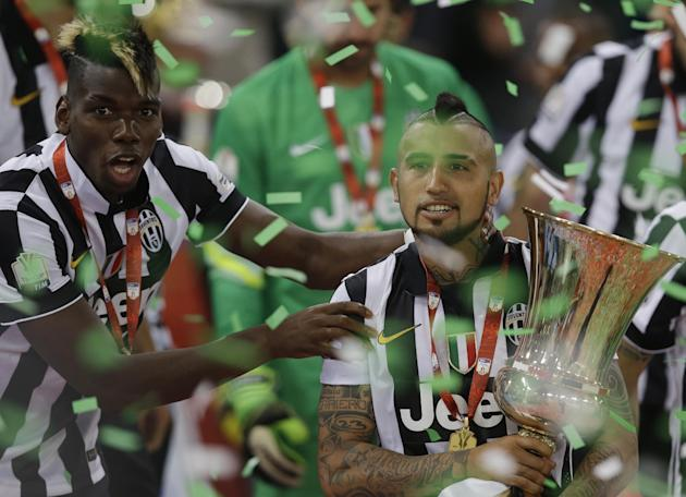 Juventus' Arturo Vidal, right, and teammate Paul Pogba celebrate with the trophy at the end of the Italian Cup soccer final match between Lazio and Juventus at Rome's Olympic stadium, Wednesda