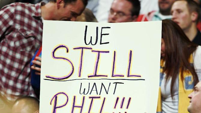A Los Angeles Lakers fan hoists up a placard in support of retired Lakers head coach Phil Jackson as the Lakers play against the Denver Nuggets in the fourth quarter of the Nuggets' 111-99 victory in an NBA basketball game in Denver on Wednesday, Nov. 13, 2013