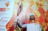 Russian ice dancer Ilia Averbukh holds the newly unveiled Sochi 2014 Olympic Torch during a press conference in Moscow, on January 14, 2013