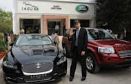 Tata Motors Passenger Car Business Unit president Rajiv Dube poses in front of Jaguar and Land Rover cars