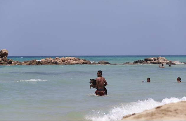 A man carries a dog in the sea in Deriana