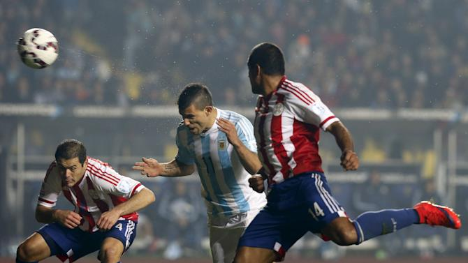 Argentina's Sergio Aguero heads the ball to score a goal past Paraguay's Paulo Da Silva as Paraguay's Pablo Aguilar looks on during their Copa America 2015 semi-final soccer match at Estadio Municipal Alcaldesa Ester Roa Rebolledo in Concepcion