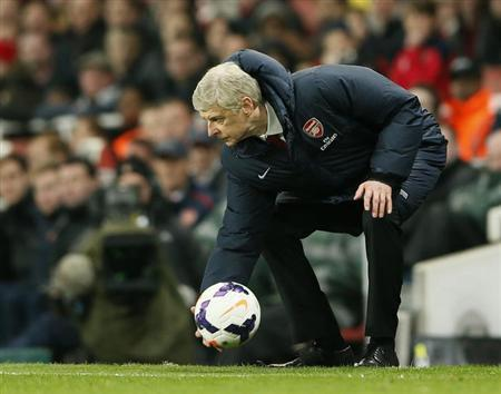 Arsenal manager Arsene Wenger picks up the ball during their English Premier League soccer match against Swansea City at the Emirates stadium in London March 25, 2014. REUTERS/Stefan Wermuth