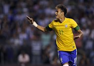 Brazil's forward Neymar celebrates after scoring a penalty kick at La Bombonera stadium in Buenos Aires on November 21, 2012. Brazil star Neymar is to stay with Santos in his homeland until at least after the 2014 World Cup, according to his father Neymar da Silva