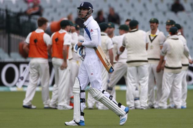 England's Broad walks off the field after his dismissal as Australia's team celebrate during the fifth day's play in the second Ashes cricket test at the Adelaide Oval