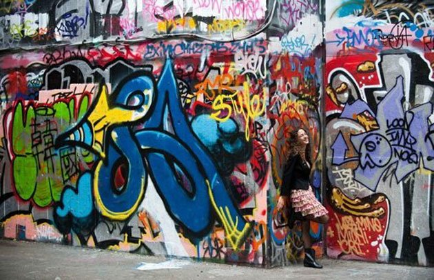 A woman poses to have her photograph taken in the graffiti and street art covered designated skate area on the South Bank in London on July 7, 2010. (AFP photo)